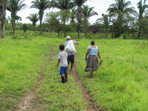 Family walking down muddy path to village